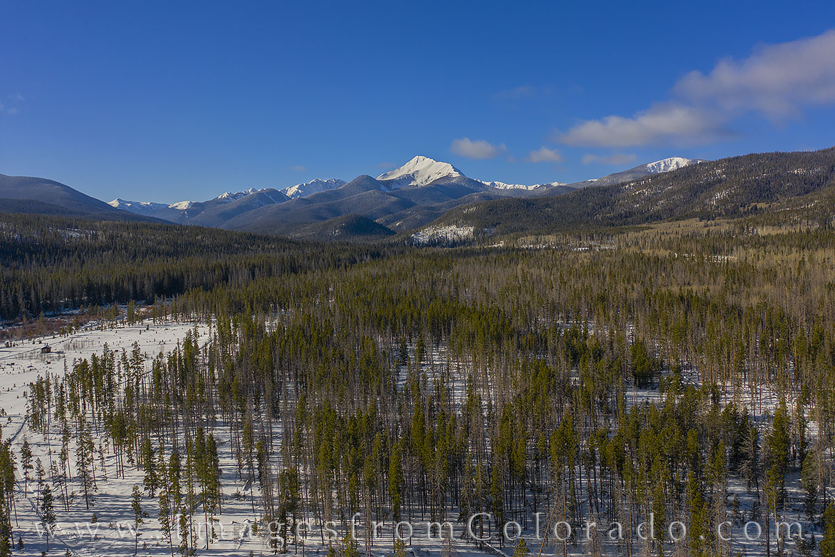 Looking across the forested valley just outside of Fraser, Colorado, this aerial view shows Byers Peak as it rises into the frigid...