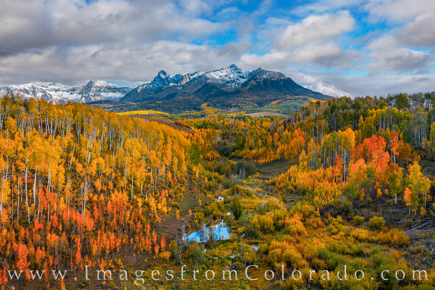 From high above a beautiful valley, the orange and gold colors of Autumn seem to glow in this late afternoon view of Hayden Peak...