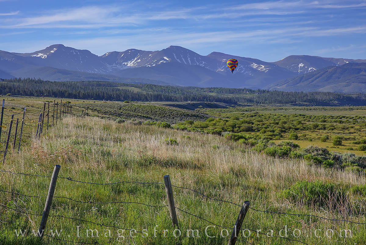 Taken with a telephoto lens near Tabernash, this photograph shows a hot air balloon as it drives across the valley between Frasher...