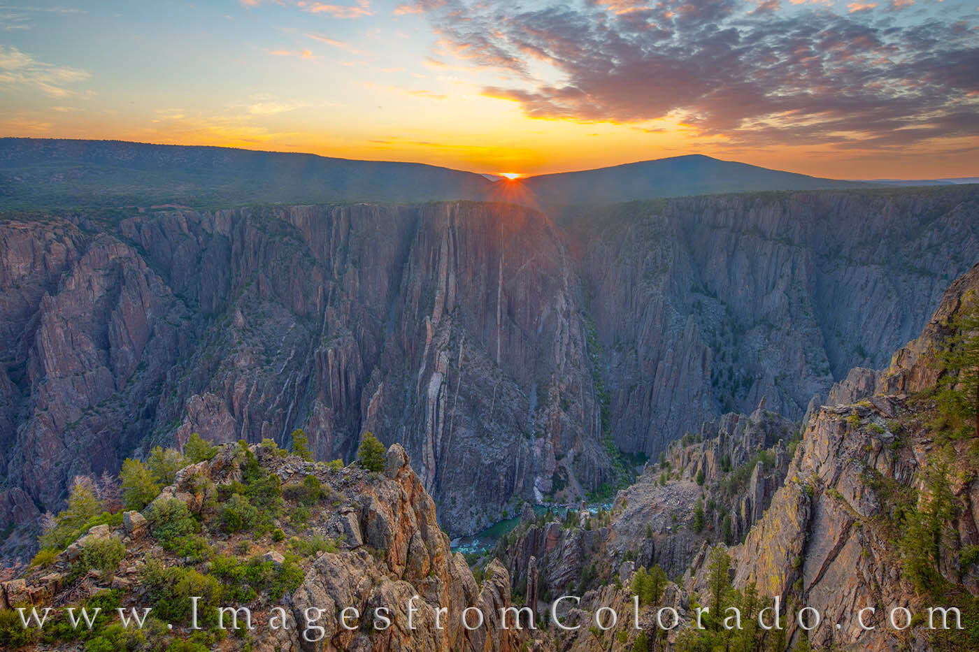 From Gunnison Point not far from the Visitor Center, the sun rises over the distant cliffs on a cool July morning. Far below...