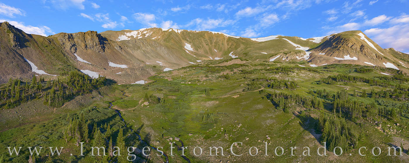 On a summer day high above Butler Gulch, the valley below is lush with summer green. The Butler Gulch trail winds up the meadow...