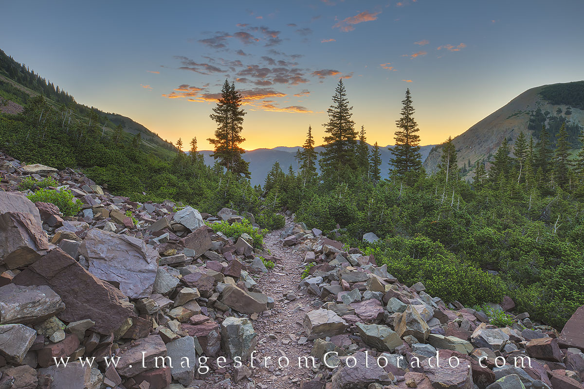 Sunrise comes to the rocky trail leading up to Cathedral Lake in the Maroon Bells Wilderness area. This photograph was taken...