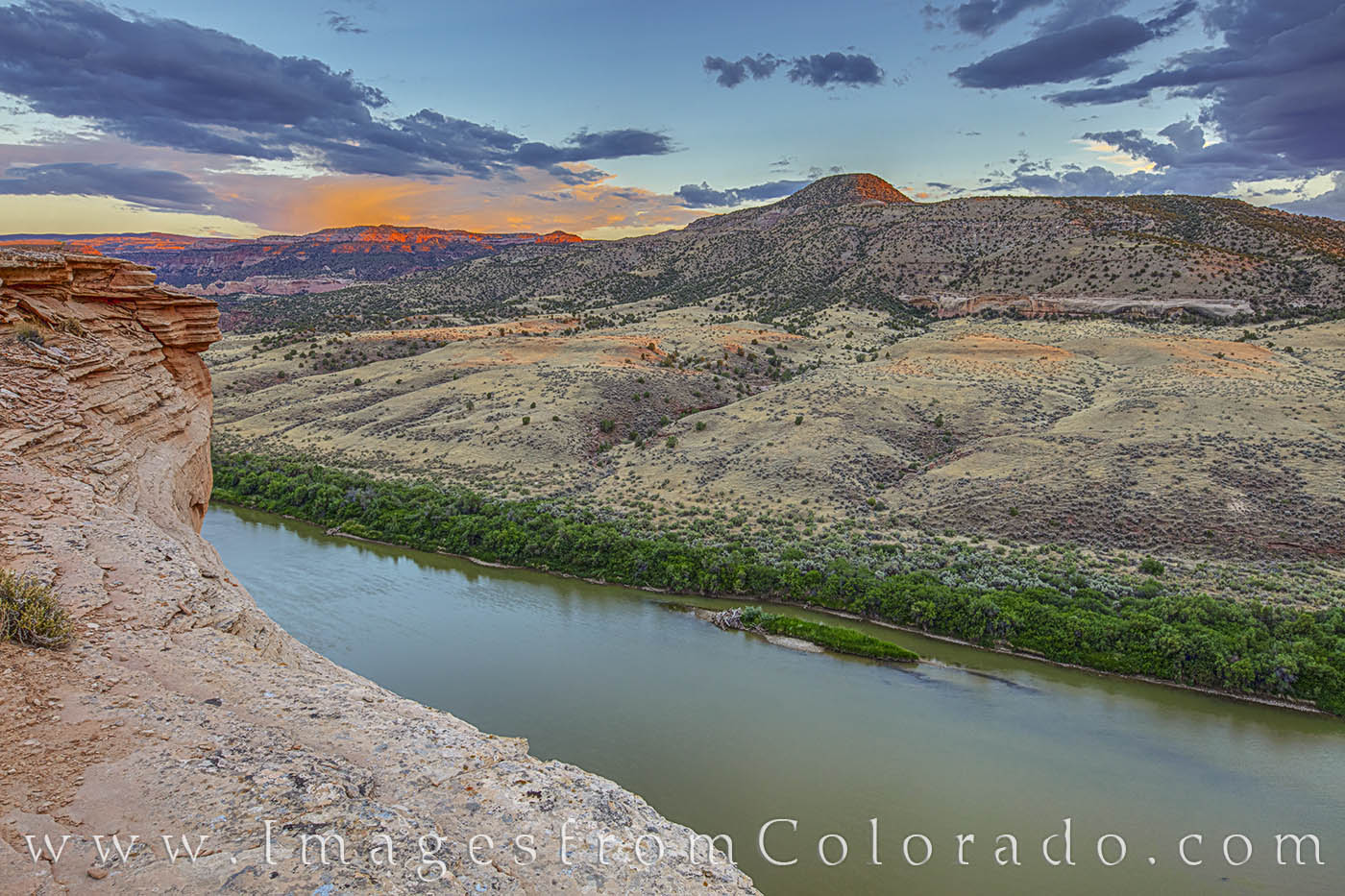 From a small promentory along the Kokopelli Trail, this view of the Colorado River looks east at sunset. In the distance is Black...