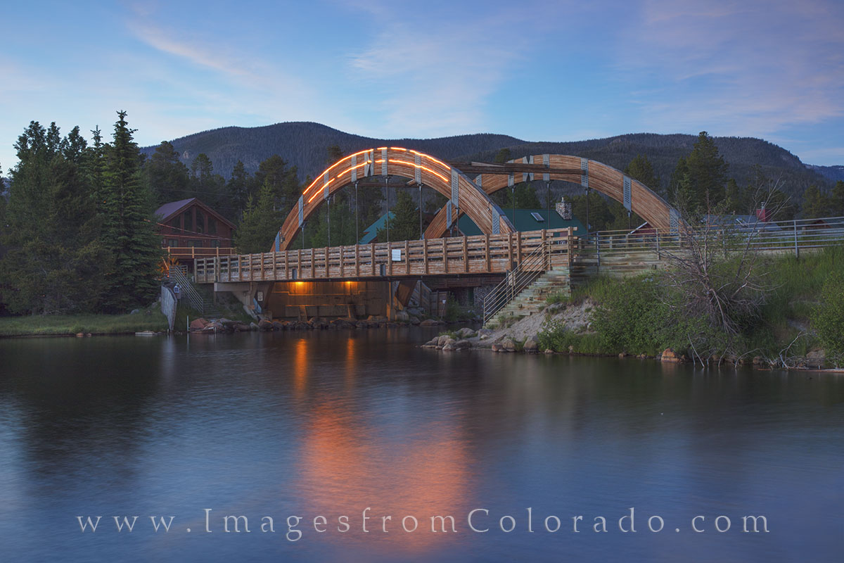 Built in 1991, this arch bridge on Jericho Road crosses over the Grand Lake Channel. In the distance, the mountains of Rocky...