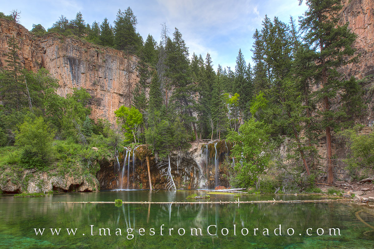 The emerald waters of Hanging Lake are surrounded by high rocky cliffs. The hike to reach this beautiful Colorado waterfall is...