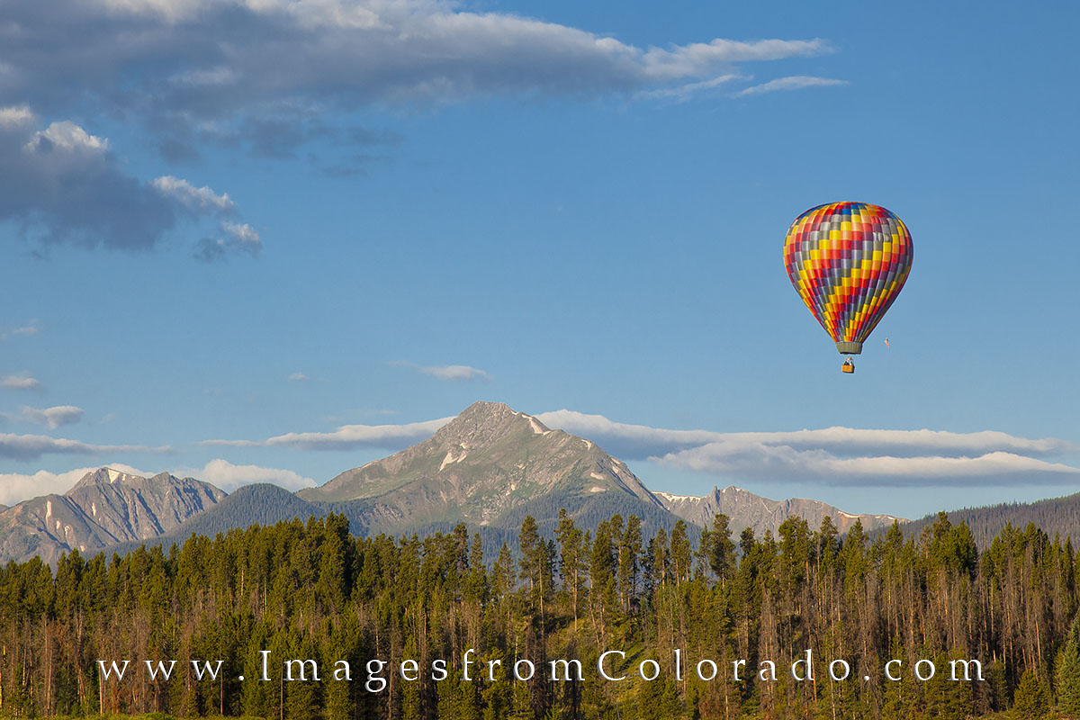 On a cold summer morning, a hot air baloon drifts over the pine trees near Fraser, Colorado. In the distance is the locally well...