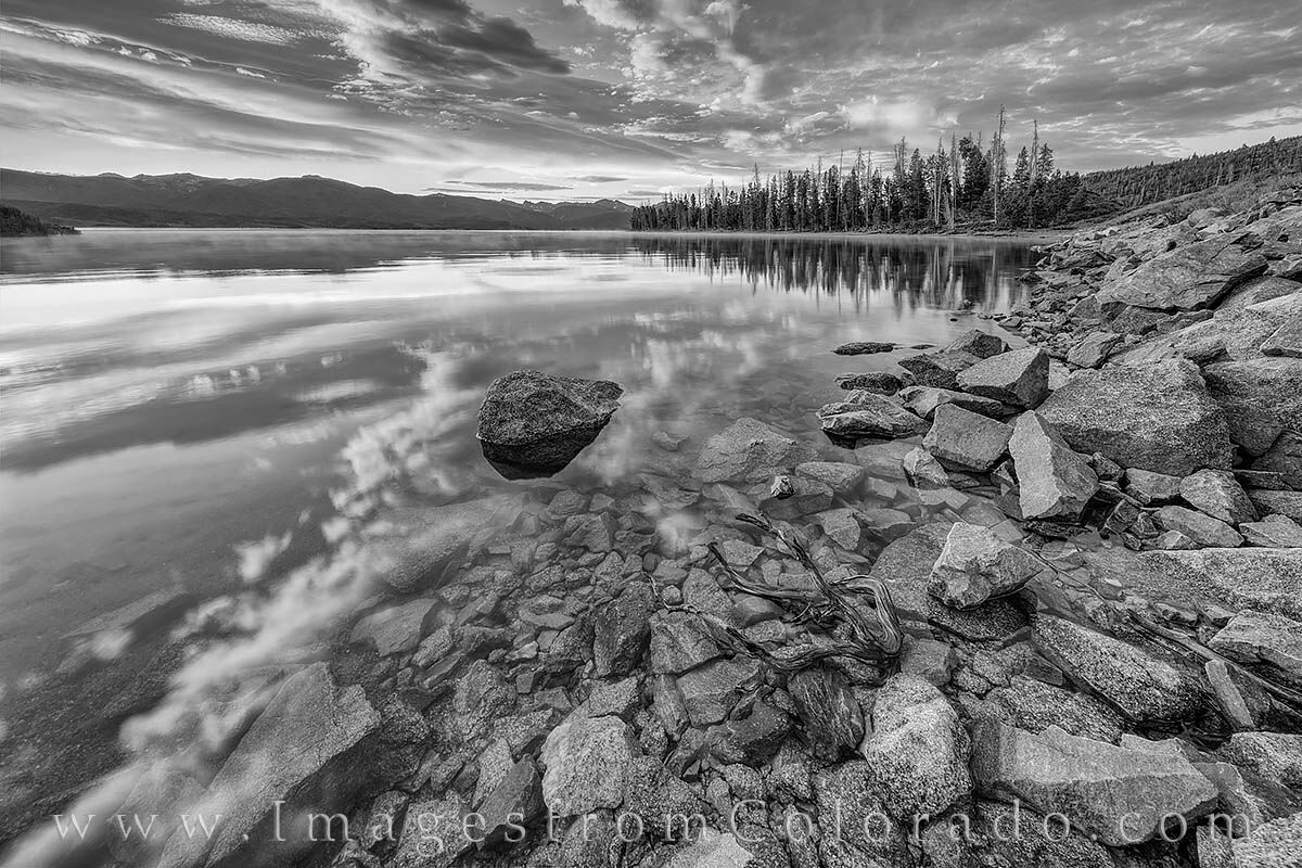 From the calm shores of Lake Granby on a quiet summer morning, the sunrise spread like a tapestry of color across the Rocky Mountain...