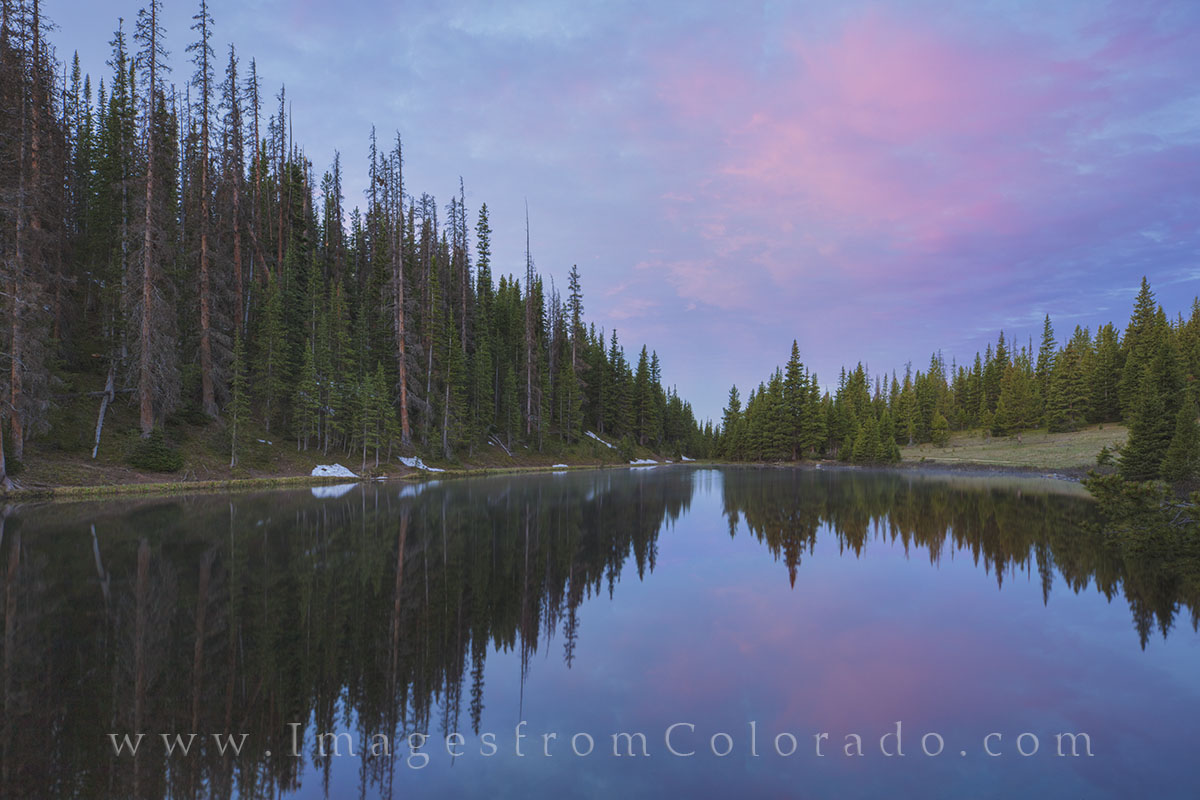 On a calm morning in Rocky Mountain National Park, Lake Irene offers a nice reflection of pink morning clouds well before sunrise...