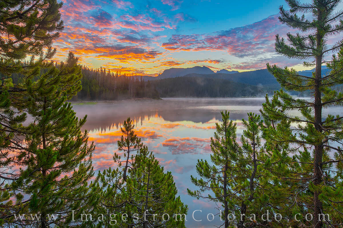 A glorious sunrise spreads across the sky above Meadow Creek Reservoir in Grand County. In the foreground the reflection Mount...