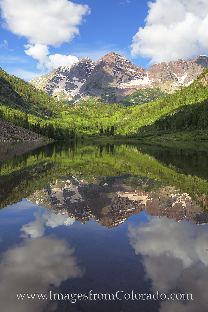 In the late morning, clouds drifted over the majestic Maroon Bells and their reflection, along with the two 14ers peaks, were...