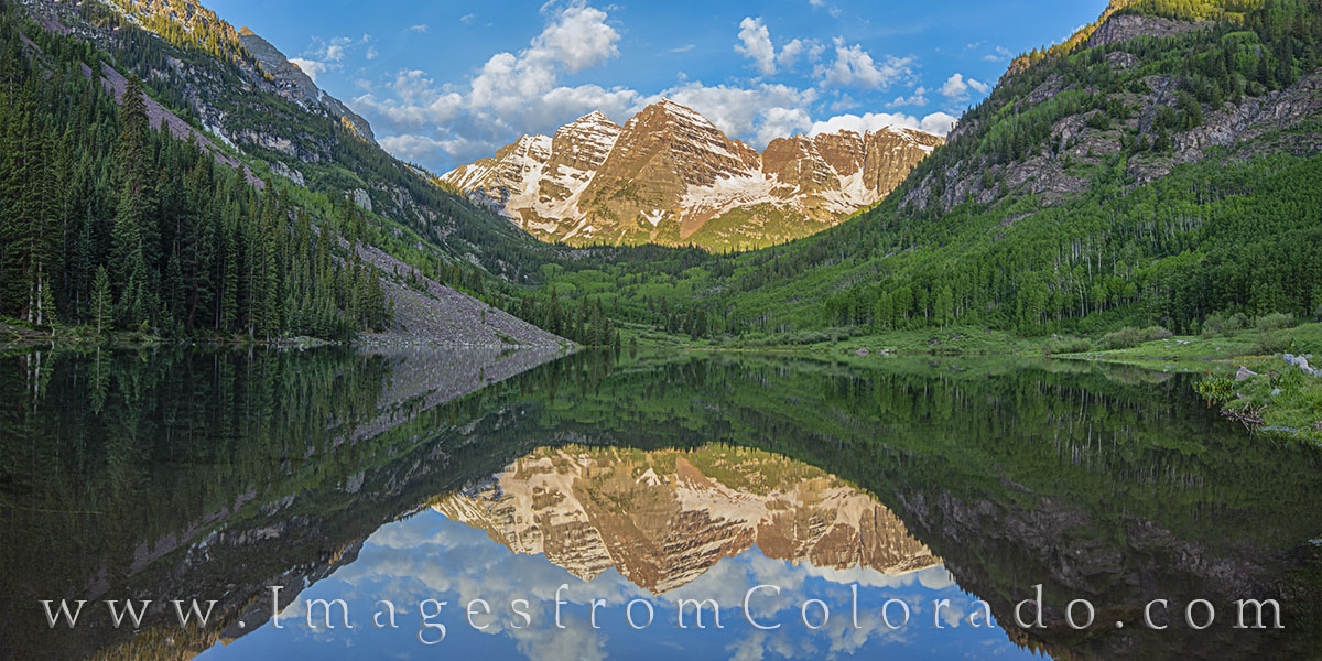 On a pristine summer morning at the Maroon Bells, Maroon Lake is smooth and offers a mirror-like reflection of the iconic Maroon...
