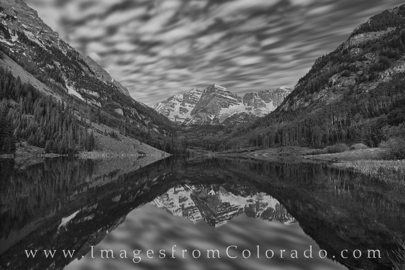 In this 135 second exposure from Maroon Lake in the Maroon Bells Wilderness area, clouds drift over the iconic 14ers, Maroon...