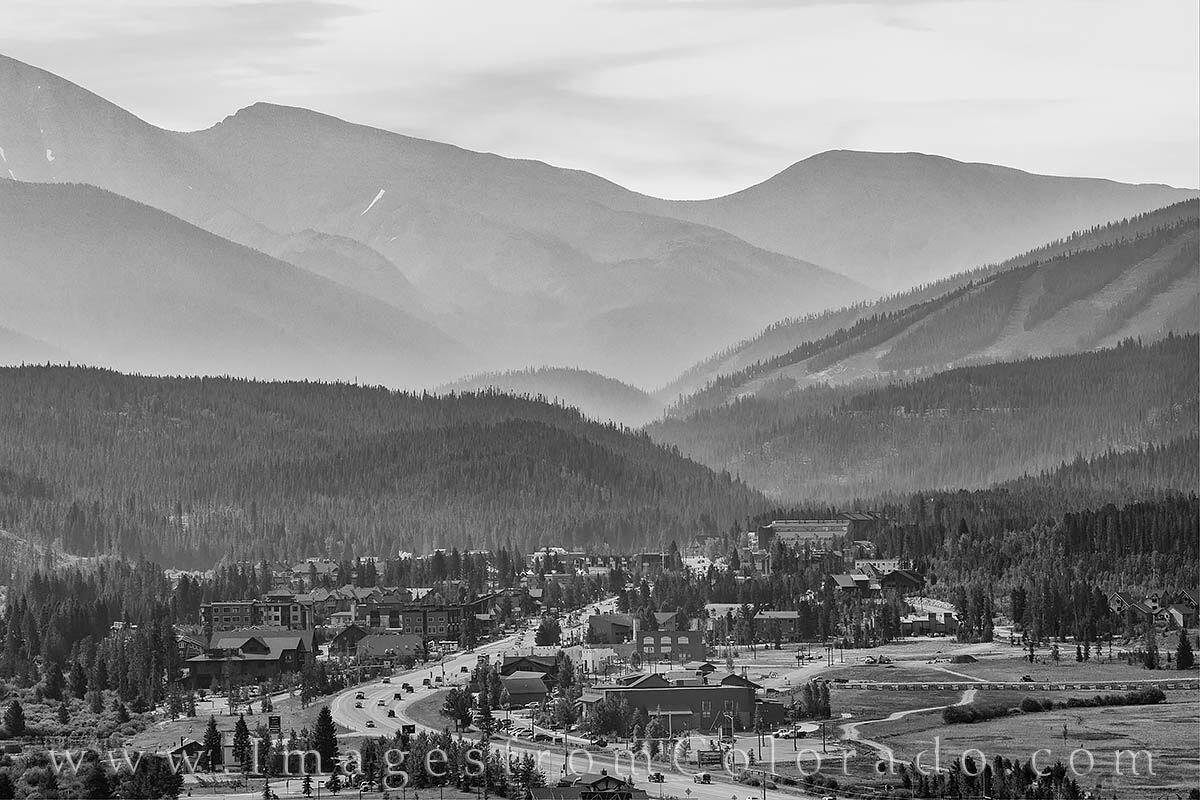 The resort town of Winter Park rests in a black and white morning of mist-layered mountains. In the foreground, Highway 40 winds...