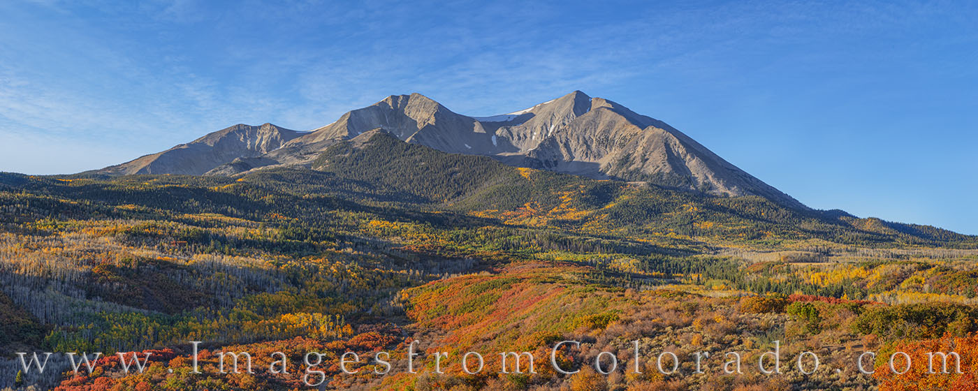 Mount Sopris rises to 12,966' above the valley. In the foreground, fall colors or red and orange and gold fill the slopes on...