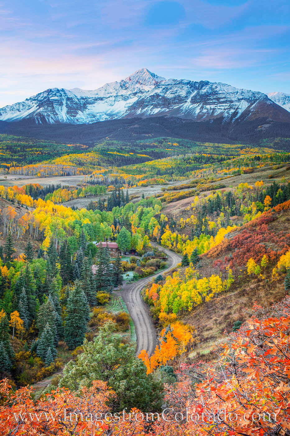 From a ridge high above a small dirt road, this view captures Mount Wilson in the distance with colorful aspen and scrub brush...