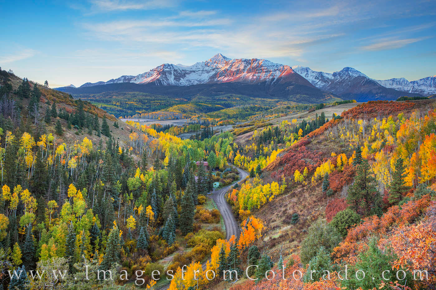 First light spreads across the snowy slopes of Mount Wilson in the San Juan Mountains. Autumn colors spread across the valley...