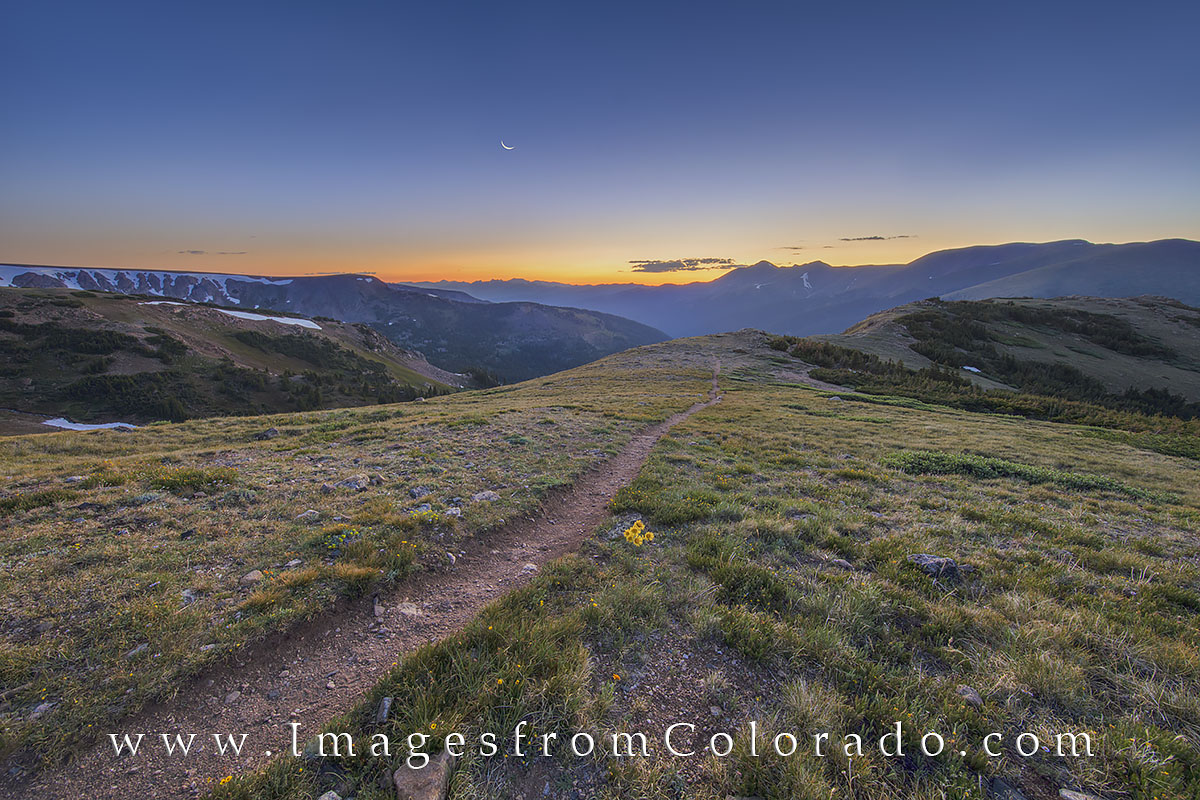 The crescent moon rises in the east just ahead of sunrise on this cold July morning atop the Continental Divide Trail. Just a...