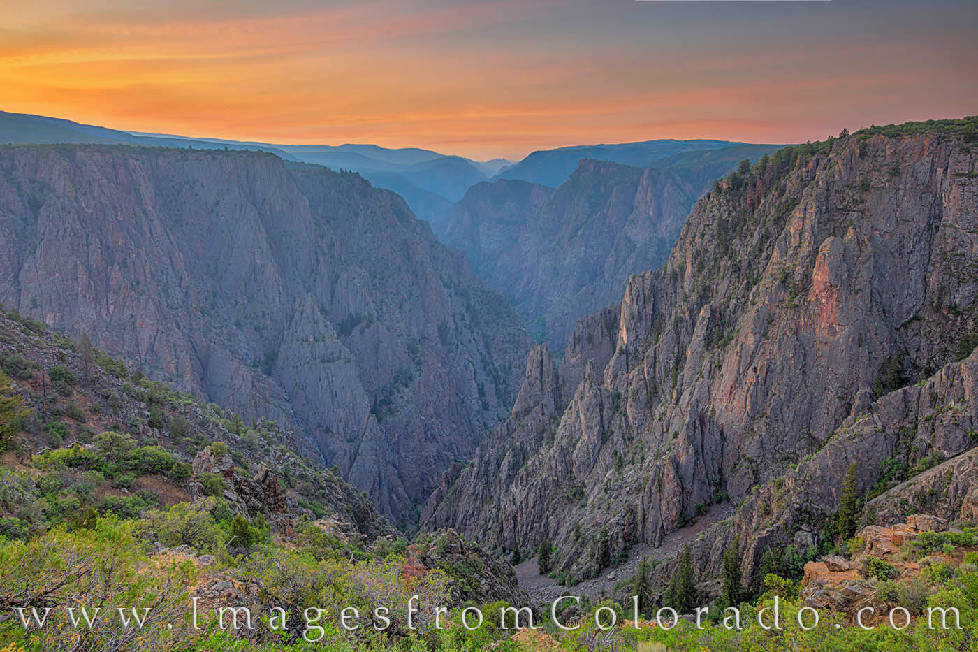 The sky was lit in shades of orange over the Black Canyon of the Gunnison on this summer morning. This deep gorge surrounded...