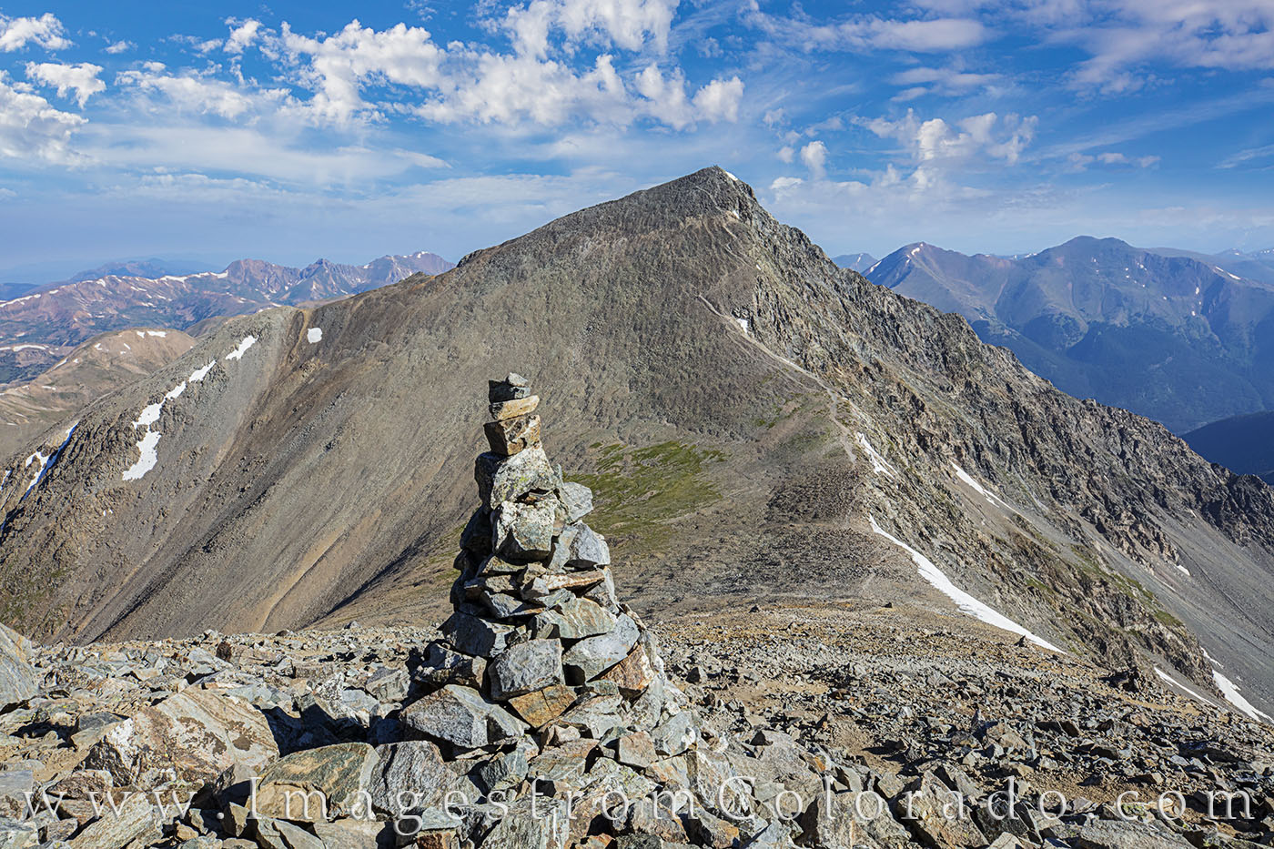 A cairn marks the path down from Grays Peak (14,270') to the saddle and back up to Torreys Peak (14,267'). The skies were...