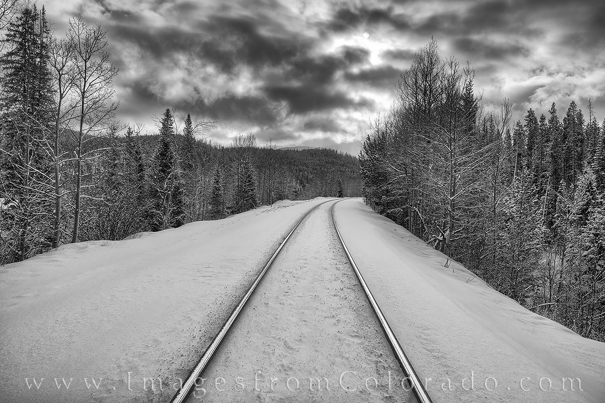 After a snow, these train tracks are just two rails riding on a bed of white. Taken in Grand County near Winter Park, this photograph...
