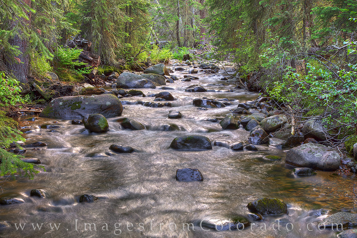 The last light of day tints the rushing waters of Vasquez Creek near Winter Park, Colorado, a soft shade of orange. This one...