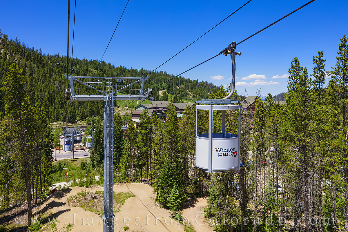 This Winter Park photograph shows one of the many gondolas that transports folks up the mountain or to the base.. Summertime...